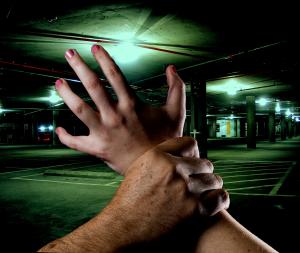 male hand grabs female wrist in dim parking garage