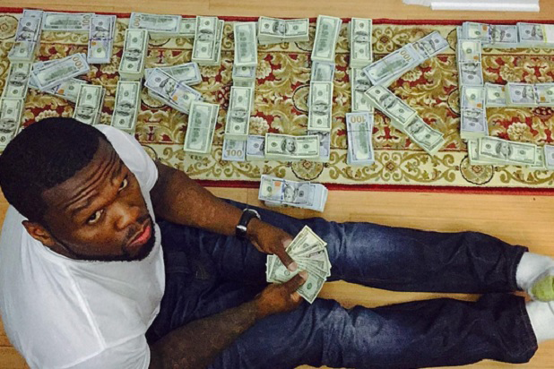 "50 Cent sits on the floor next to piles of cash that spell ""BROKE"""