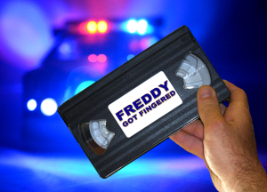 """A hand holds a VHS tape of """"Freddy Got Fingered"""" in front of flashing police lights"""