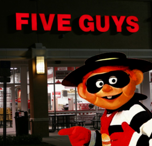 the hamburglar stands outside a Five Guys restaurant at night