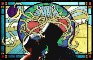 a couple with colanders on their heads kiss in front of a stained glass window depicting the Flying Spaghetti Monster