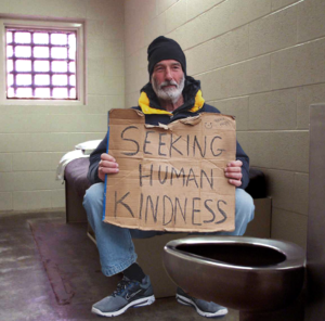 """homeless man holds a sign reading """"seeking human kindness"""" while sitting in jail cell"""