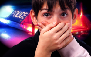 kid covering his mouth after burp with police car in background