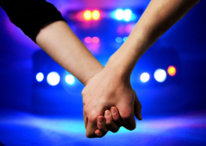 mother and son hold hands in front of police lights