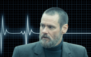 jim carrey looks sad in front of a flat lining life support system