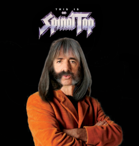 harry shearer dressed as his spinal tap character stands under the spinal tap logo