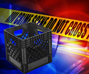 a milk crate sits in front of police lights and crime scene tape