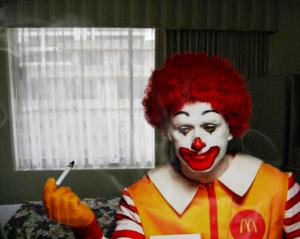 ronald mcdonald chain smokes in a gloomy motel room
