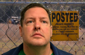 """Todd Kohlhepp stands before a fence with a """"no trespassing"""" sign"""